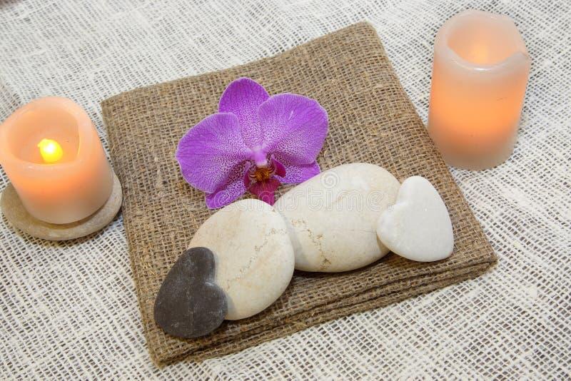 按摩、蜡烛和兰花花的石头在自然自然餐巾,宜人的口气,温泉的 库存图片