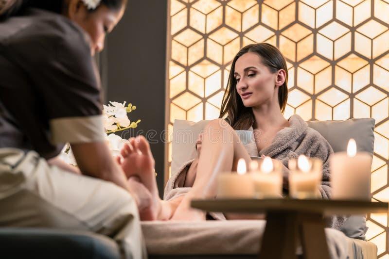 按摩一个女性客户的脚的亚洲秀丽的治疗师 免版税库存图片
