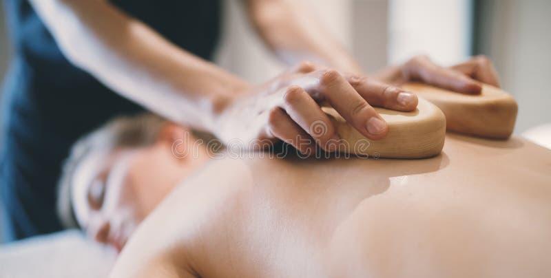 按摩使用木工具的治疗师按摩患者 库存照片