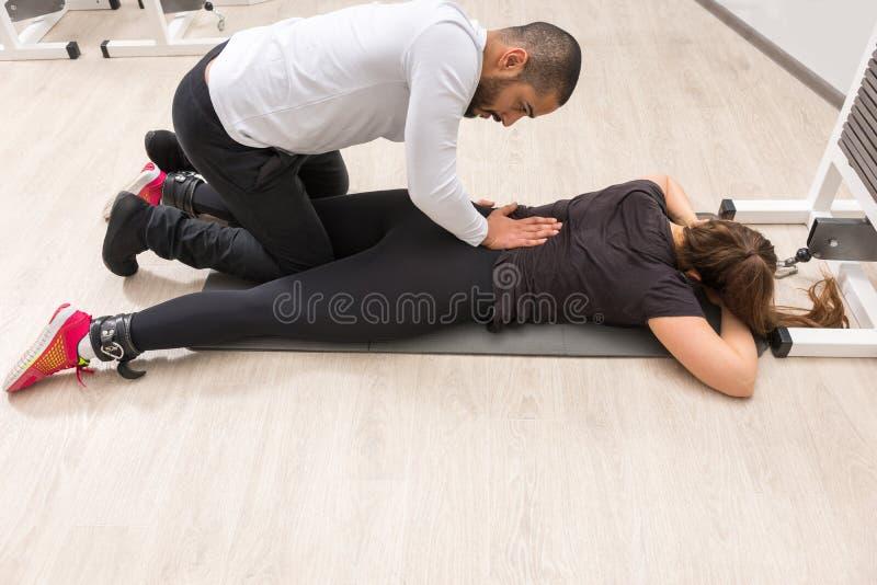 按摩健身房的妇女的教练员 库存图片