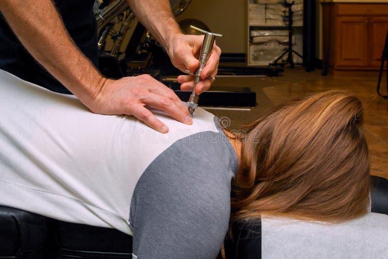 按摩医生使用一个积分器在少女背面 免版税图库摄影