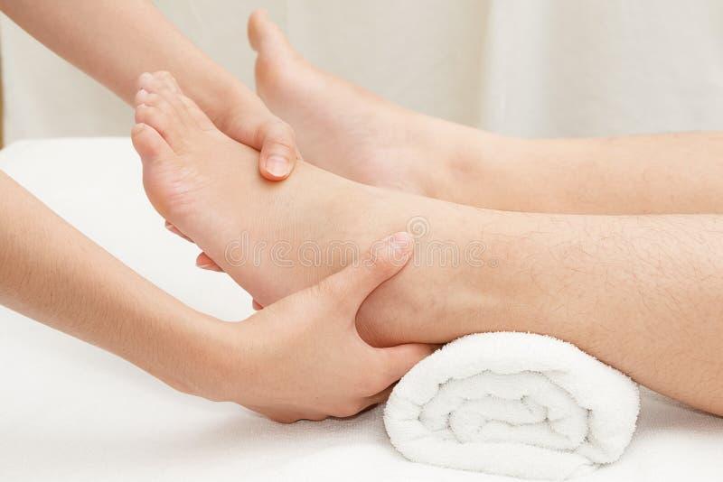 按摩女性脚的治疗师的手 库存图片