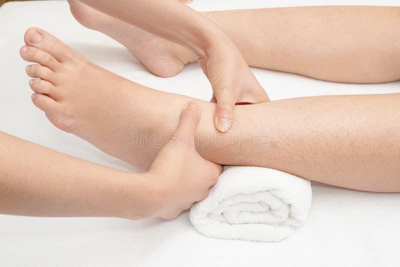 按摩女性脚的治疗师的手 免版税库存图片
