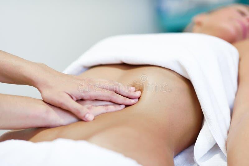 按摩女性腹部的手 施加压力在的治疗师是 库存照片