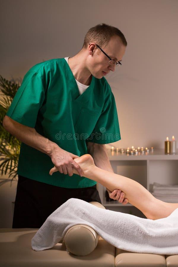 按摩女性腿的生理治疗师 免版税库存照片