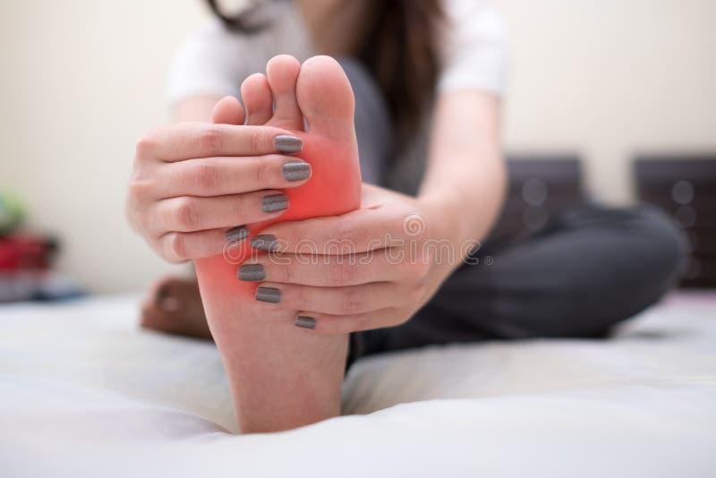 按摩她的痛苦脚的少妇 背景弄脏了关心概念表面健康防护屏蔽的药片 免版税图库摄影