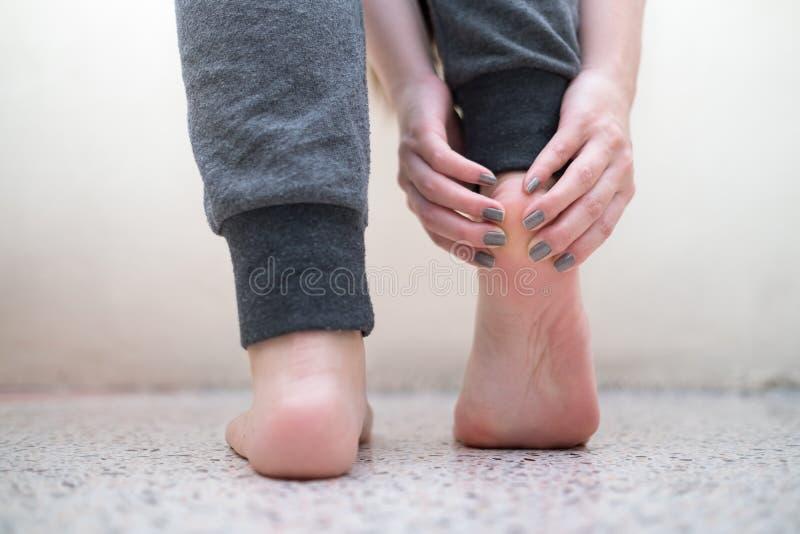 按摩她的痛苦脚腕的少妇 背景弄脏了关心概念表面健康防护屏蔽的药片 库存图片