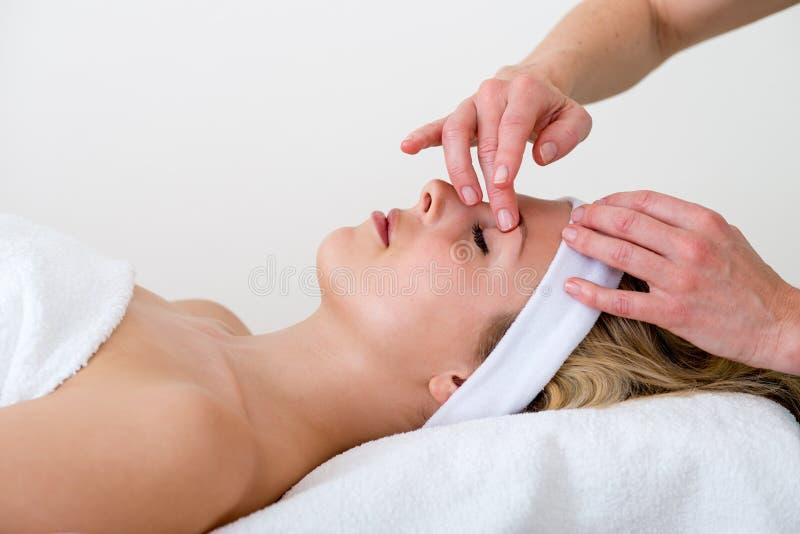 按摩妇女眼眉区域的女按摩师。 免版税图库摄影