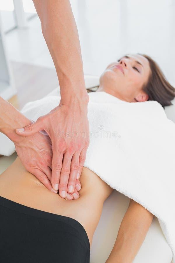 按摩妇女身体的生理治疗师的特写镜头 免版税库存照片