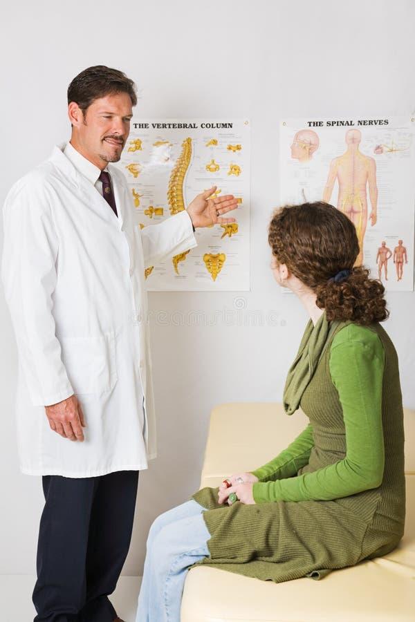 按摩师列解释脊髓 图库摄影