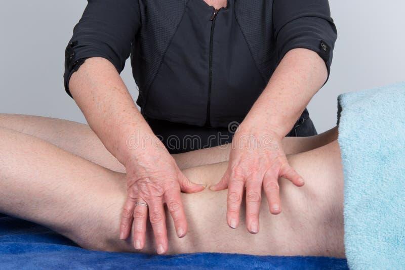 按摩患者的腿在温泉中心 免版税库存图片