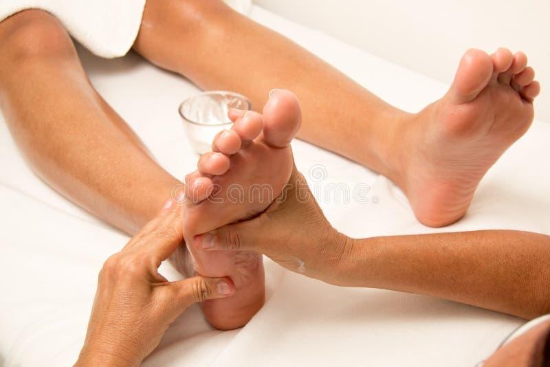 按摩按摩一只妇女` s脚的治疗师 库存图片