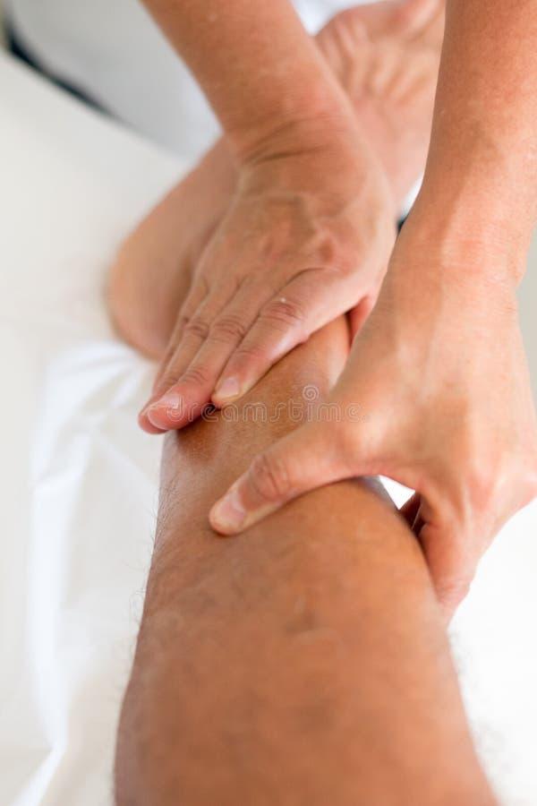 按摩按摩人` s腿的治疗师 图库摄影