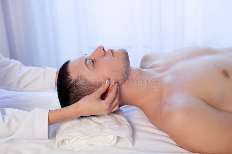 按摩治疗师做一个人按摩疗法温泉脸面护理 库存图片