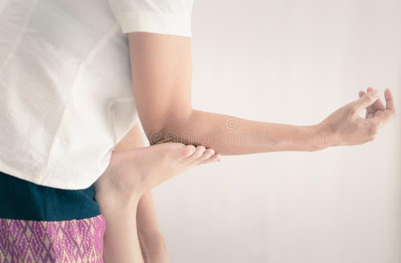 按摩治疗师在脚使用手肘推挤 免版税库存照片