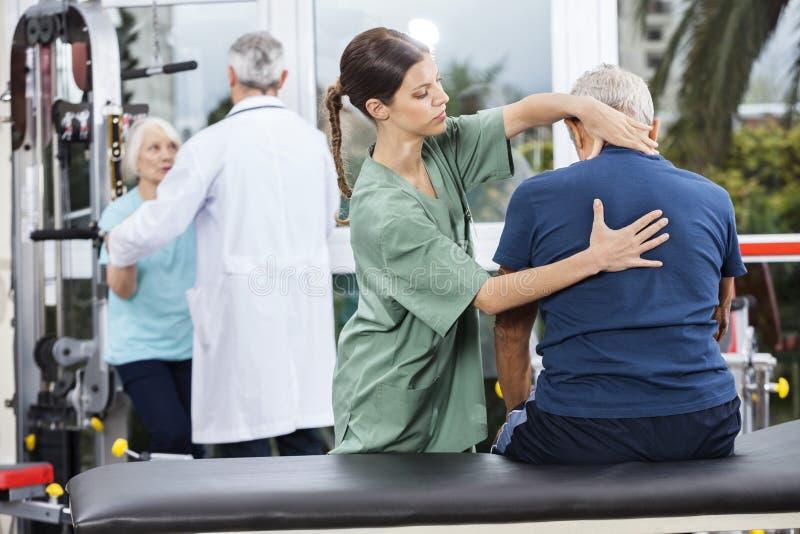 按摩老人的后面的生理治疗师 免版税库存图片