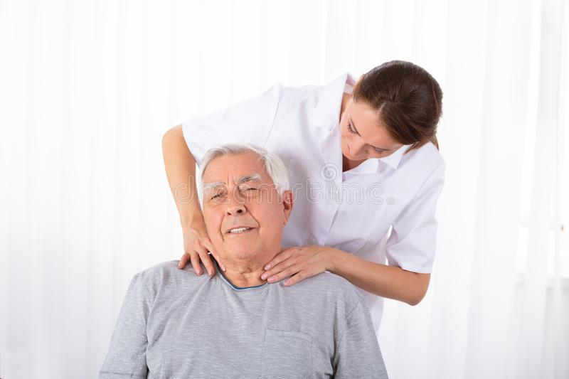 按摩老人的肩膀的生理治疗师 图库摄影