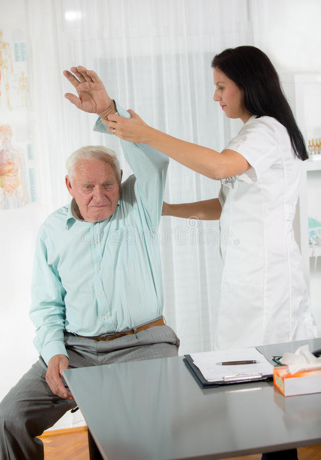 按摩脊柱治疗者:审查老人的按摩医生在办公室 图库摄影