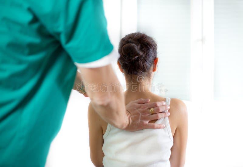 按摩医生按摩女性耐心脊椎和后面 免版税库存照片