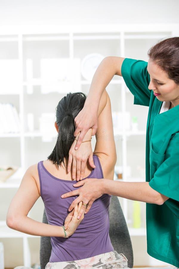 按摩医生按摩女性耐心脊椎和后面 免版税库存图片
