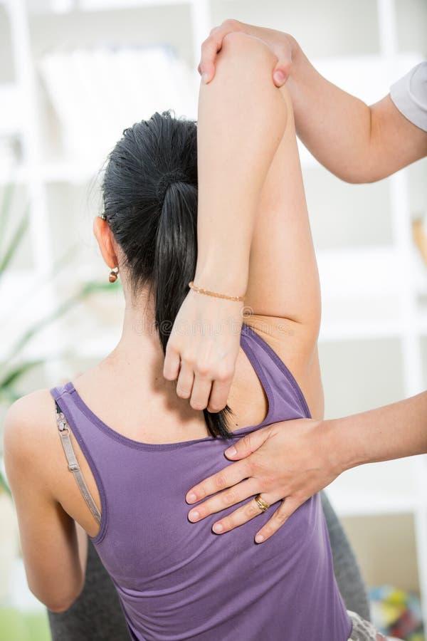 按摩医生按摩耐心脊椎和后面 图库摄影