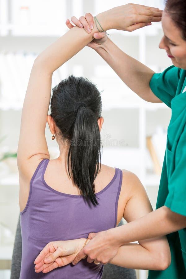 按摩医生按摩耐心脊椎和后面 免版税库存图片