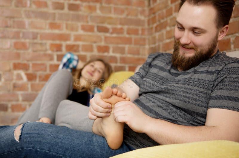 按摩他的恋人` s脚的年轻人 免版税库存照片