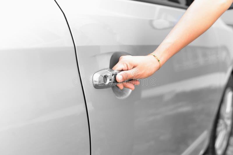 按汽车把柄的按钮手妇女 库存照片