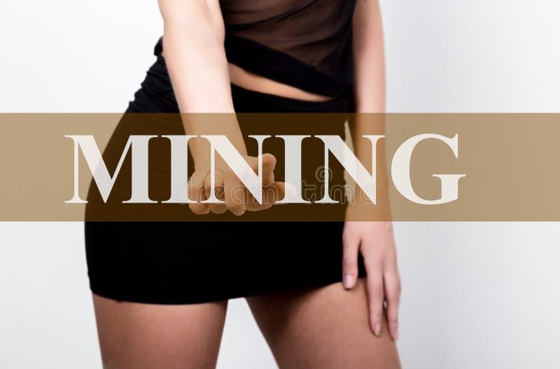 按触摸屏幕的采矿按钮的短裙的女实业家 隐藏货币概念的交换和生产 图库摄影
