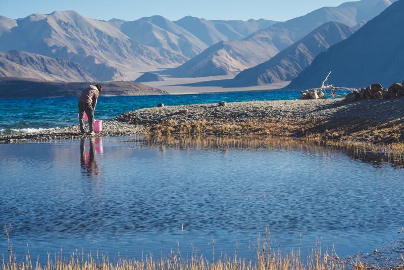 挖出水的一个人在Pangong湖用山景和蓝天 免版税库存图片