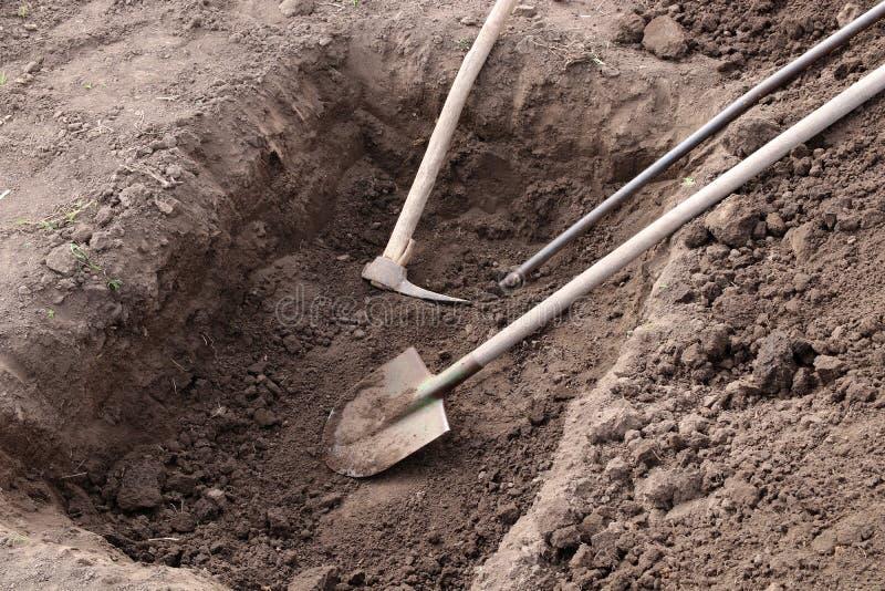 挖坑 铲子、镐和撬棍都躺在坑里 库存图片
