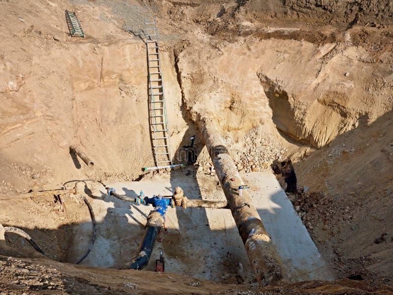 挖掘坑 老500mm喝有150mm垄断的胳膊的水管有闸式阀的 库存照片