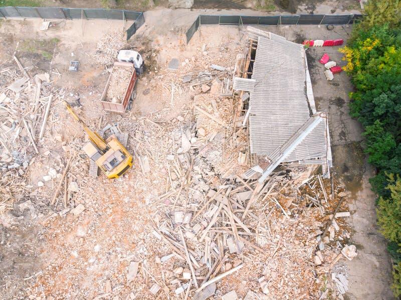 挖掘机和清理站点的翻斗车在大厦的爆破以后 图库摄影