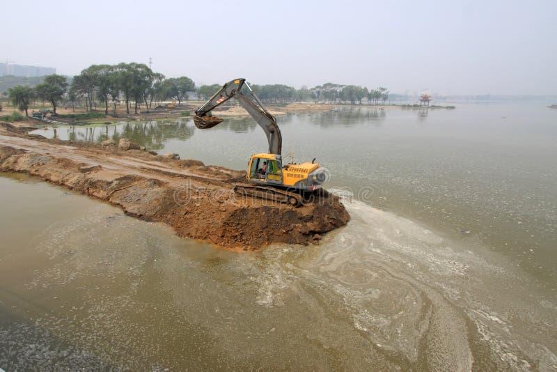 挖掘机在水坝建造场所 免版税库存照片