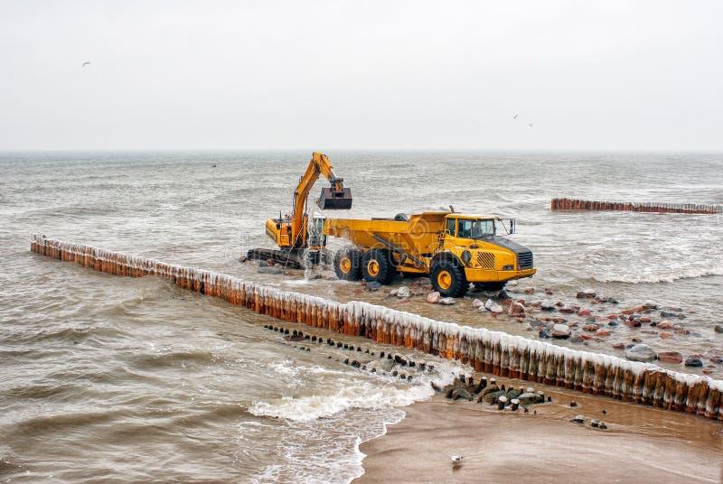 挖掘机在海滩的装载的卡车石头 免版税库存图片