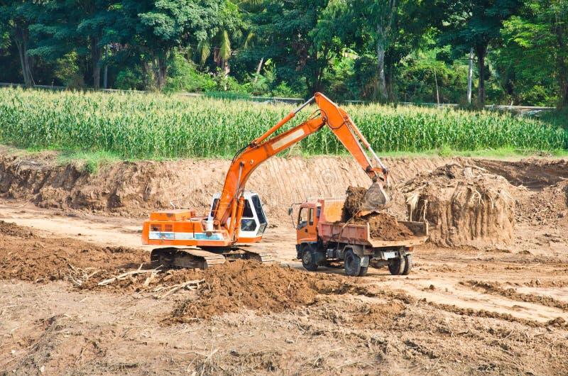 挖掘机大量装入程序移动土壤工作 库存照片