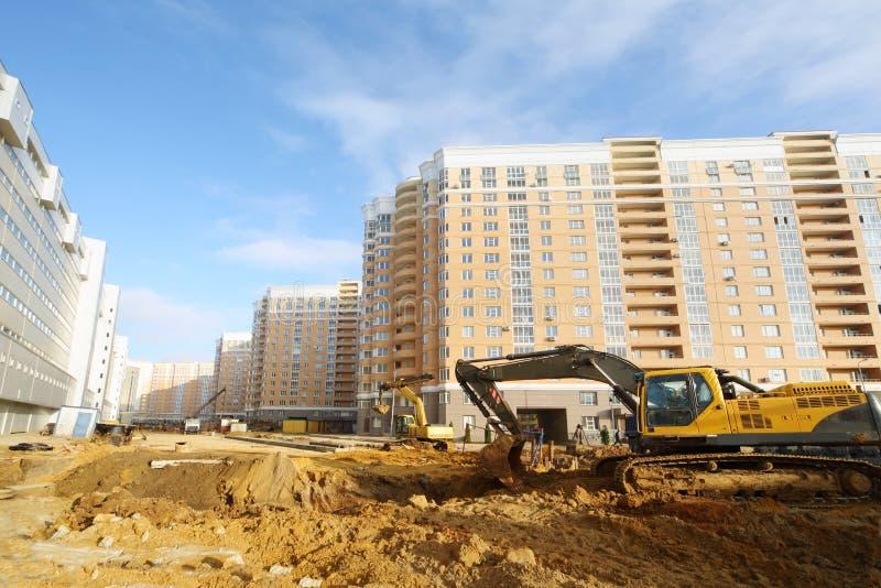 挖掘机开掘地面近的高多层的大厦 免版税库存图片