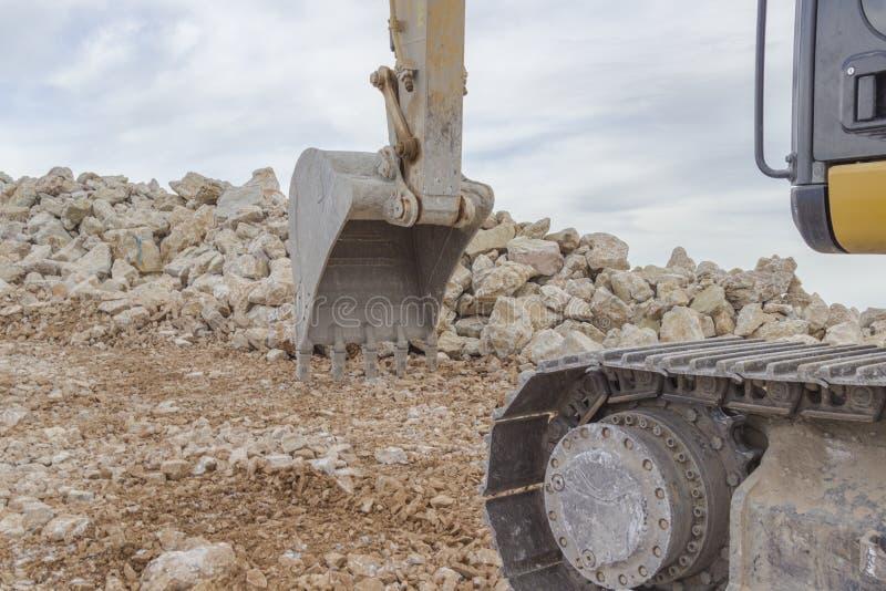 挖掘机斗和履带与石头和天空的对抗 免版税图库摄影