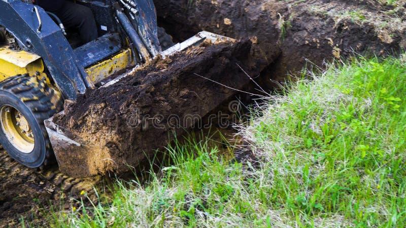 挖掘机桶播种的看法有土壤的在它在象草的领域的地球工作 免版税库存图片