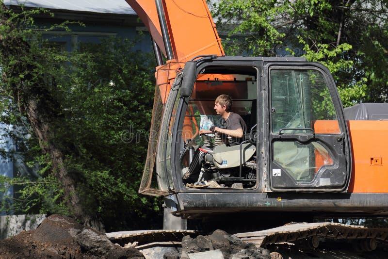 挖掘机的司机在工作 免版税库存图片