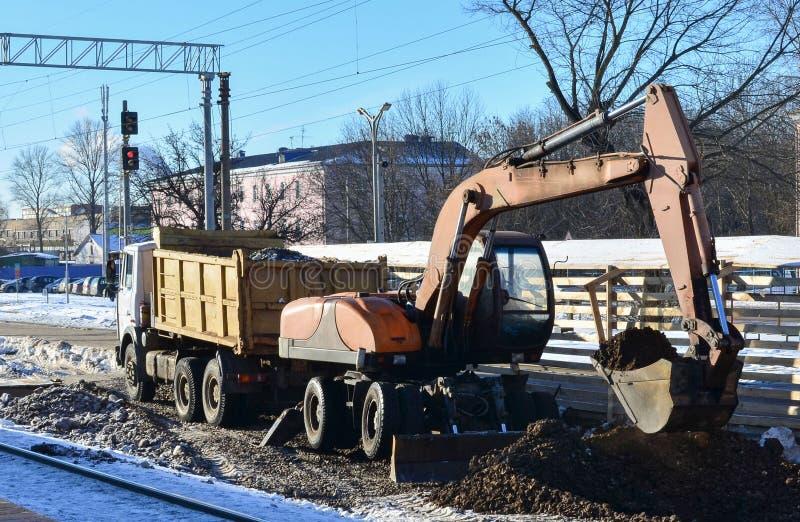 挖掘机装载击碎了石在翻斗车身体 铁路的建筑 地球的表面为放置做准备 库存图片