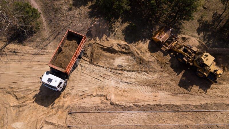 挖掘机装载的沙子到有航拍寄生虫的一辆卡车里 免版税库存图片