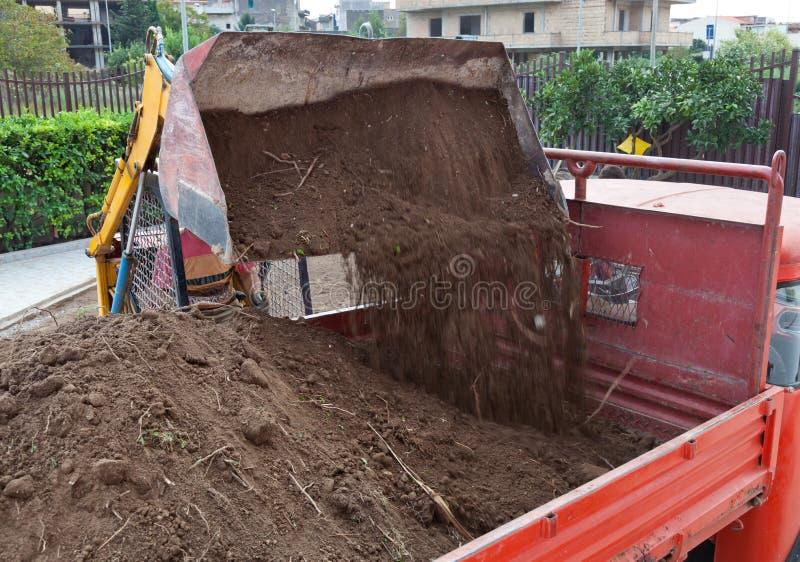 挖掘机装货倾销者卡车卸车 库存图片