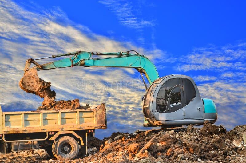 挖掘机装货倾销者卡车卸车 免版税库存照片