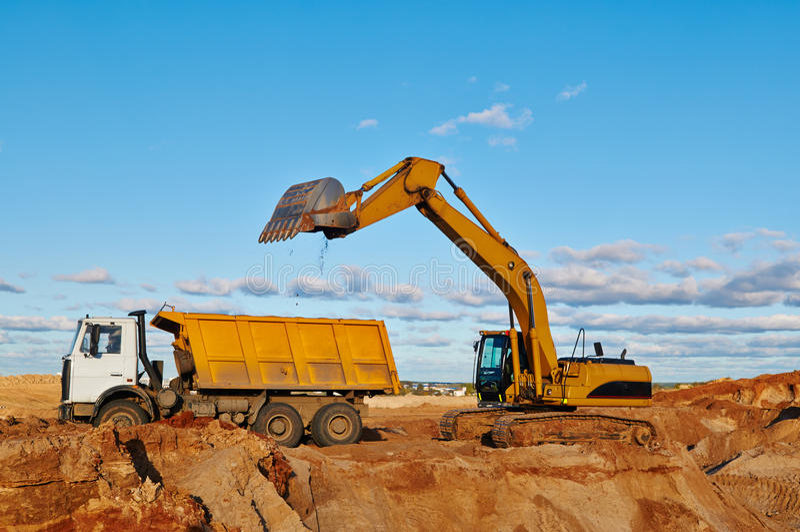 挖掘机装货倾销者卡车 免版税库存图片