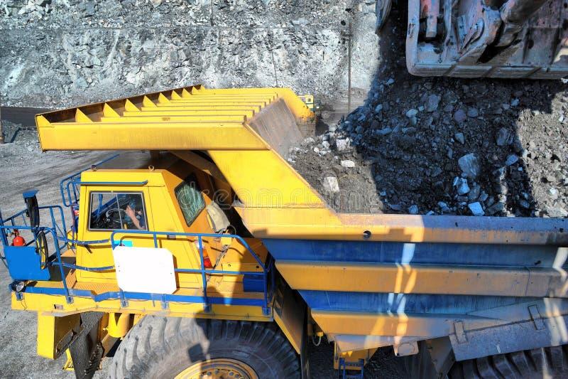 挖掘机装货铁矿到重的翻斗车里 图库摄影