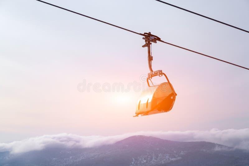 挡雪板和滑雪者专业成套装备的爬上电车推力山在天空、太阳和山峰背景  免版税图库摄影