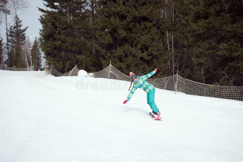 挡雪板在高速公路的女孩骑马下来从山 库存图片