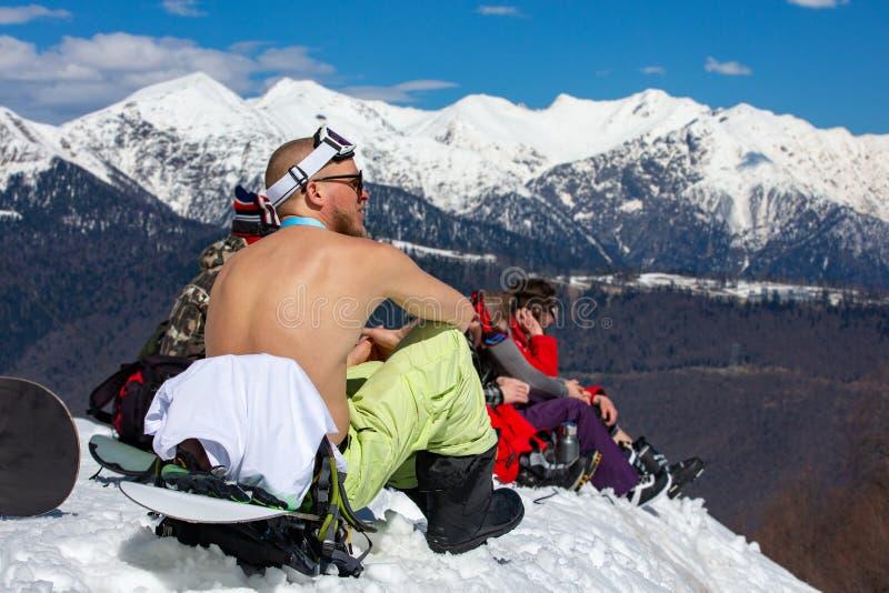 挡雪板坐露胸部在多雪的山顶和晒日光浴 免版税库存照片