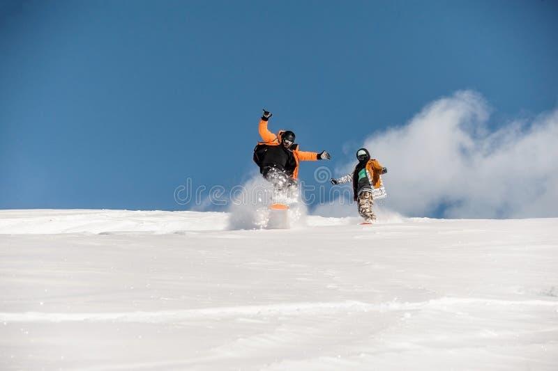 挡雪板夫妇运动服骑马的在粉末山坡 免版税库存图片